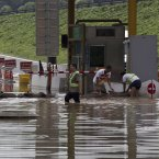 Workers puts sandbags to block flood water entering the toll gate in Fangshan district of Beijing (AP Photo/Andy Wong)