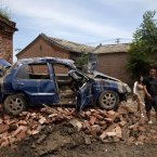 Chinese people walk past a flood damaged vehicle on the bricks at a village in Fangshan district of Beijing (AP Photo/Andy Wong)