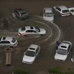 Vehicles are submerged at a flooded residence community (Photo by ChinaFotoPress) 