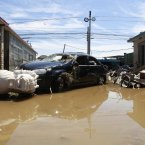 A damaged vehicle is seen after floodwaters receded (Photo by ChinaFotoPress)