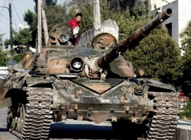 A Syrian boy sits atop a damaged tank in Azaz, 32km from Aleppo.