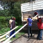 James Hennessy (centre) and colleagues transporting materials for their greenhouse to the farm