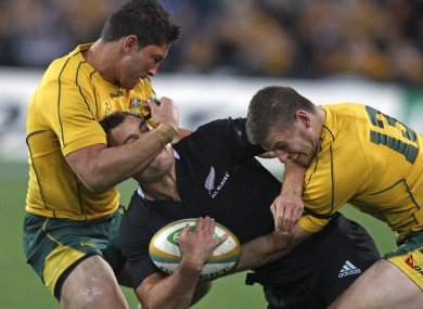 New Zealand's Israel Dagg, center, is tackled by Australia's Anthony Fainga'a, left, and Rob Horne.