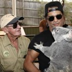 Slash is holding a koala named Tinkerbell. (AP Photo/Tertius Pickard)