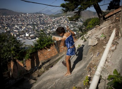 A girl sweeps up in the Chatuba slum, inside the Penha complex, in Rio de Janeiro.