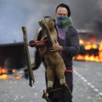 A masked man carries a toy backdropped by a burning car and garbage bins set on fire by rioters in Hackney, east London. (AP Photo/Lefteris Pitarakis)