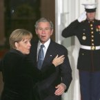 An awkward mid-embrace pause between George W Bush and Angela Merkel back in 2008. It's going to be hard to get that hug back on track. (AP Photo/Lawrence Jackson/PA Wire)