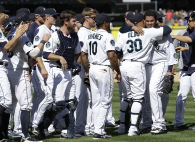 Teammates congratulate Seattle Mariners pitcher Felix Hernandez.