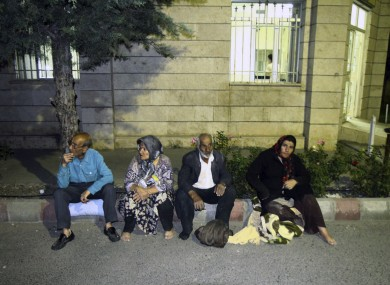 Residents sit at the side of a street after the earthquake