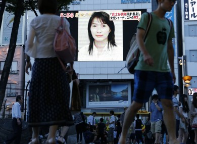 A portrait of Mika Yamamoto shown on a large monitor screen in Tokyo today