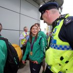 Olympic gold medalist Katie Taylor is congratulated by a member of the airport police.