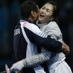 South Korea's Kim Ji-yeon gets a hug from her coach after defeating Russia's Sofya Velikaya during the gold meal match in women's individual sabre fencing competition at the 2012 Summer Olympics(AP Photo/Andrew Medichini)