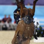 Hwang Woojin, of South Korea, and his horse Shearwater Oscar, fall down after the horse bucked after the starting bell sounded to start their run in the equestrian show jumping stage of the men's modern pentathlon at the 2012 Summer Olympics. (AP Photo/David Goldman)