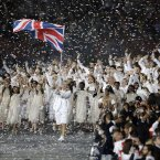 Great Britain's Chris Hoy carries the national flag as confetti surrounds the team during the Opening Ceremony at the 2012 Summer Olympics, Friday, July 27, 2012, in London. (AP Photo/Mark Humphrey)