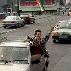 A woman celebrates the news on 31 August in a cavalcade of cars on the Falls Road in Belfast. Image: Mccullou/PA Archive/Press Association Images