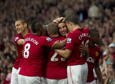 Van Persie is mobbed by his team-mates.