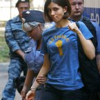 Nadezhda Tolokonnikova, a member of feminist punk group Pussy Riot greets her supporters as she is escorted to a court room in Moscow. On Friday, the three women were found guilty of hooliganism motivated by religious hatred for staging an anti-Putin protest at a Moscow cathedral. (AP Photo/Alexander Zemlianichenko)