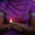 A woman takes part in a candle light vigil for the victims of the Sikh Temple of Wisconsin shooting in Milwaukee. An unidentified gunman killed six people at the suburban Milwaukee temple on Sunday in a rampage that left terrified congregants hiding in closets and others texting friends outside for help. The suspect was killed outside the temple in a shootout with police officers. (AP Photo/Jeffrey Phelps)