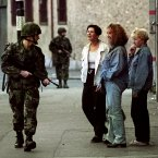 A soldier on patrol on the Falls Road, Belfast, talks to some locals following the IRA ceasefire announcement on 31 August.