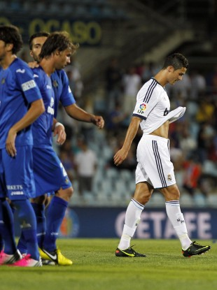 Real Madrid's Cristiano Ronaldo from Portugal, right, leaves the field as Getafe's players celebrate.