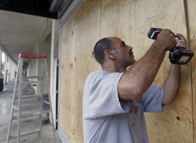 Oren Eshel boards up a shop in Key West, Florida ahead of Isaac's expected arrival today.