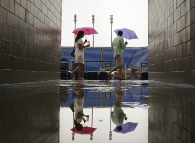 Rain, rain, go away: Spectators try to stay dry on Monday at Flushing Meadows.