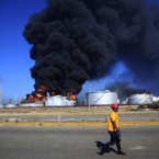 A man walks past the still-burning Amuay refinery on Sunday. (AP Photo/Ariana Cubillos/PA)