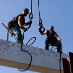 Ironworkers James Brady, left, and Billy Geoghan release the cables from the steel beam after connecting it atop the skyscraper. (AP Photo/Mark Lennihan/PA)