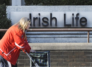 A woman passes the Irish Life headquarters in Dublin. The group has recorded profits of €116 million for the first half of 2012.