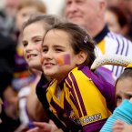 A young Wexford fan stretches to catch a glimpse of the team.
