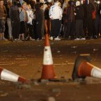 Masked Loyalist's wait to confront riot police in North Belfast last night.  (AP Photo/Peter Morrison)