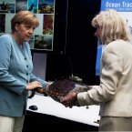 German Chancellor Angela Merkel views a tracking device attached to a model of a turtle with Sara Iverson, a marine biologist, as she visits Dalhousie University in Halifax. (AP Photo/Andrew Vaughan, The Canadian Press)