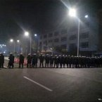 Police in anti-riot suits cordon off a road near Foxconn's plant in Taiyuan. (Mobile phone photo, via AP)