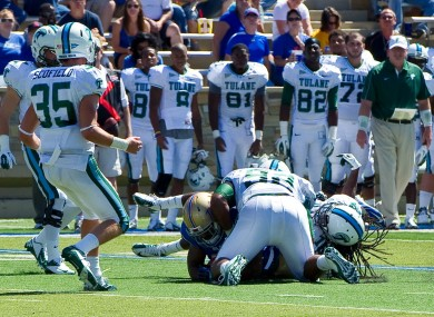 Devon Walker, bottom right, and Tulane team-mate Julius Warmsley (92) tackle Tulsa's Kenny Welcome, bottom left.