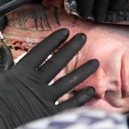 A man has a tattoo done on his head at the Eighth London International Tattoo Convention in Wapping, east London.