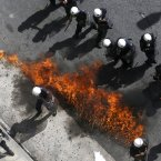 A fire bomb explodes among riot police during clashes. (AP Photo/Dimitri Messinis)