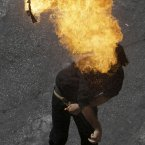 A protester throws a fire bomb toward the riot police during clashes in Athens, Wednesday Sept. 26, 2012. Police clashed with protesters hurling petrol bombs and bottles after an anti-government rally called as part of a general strike in Greece turned violent. About 50,000 people joined the union-organized march held during a general strike against new austerity measures planned in the crisis-hit country. (AP Photo/Dimitri Messinis)