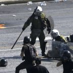 Riot police officers arrest a demonstrator, partially seen on ground, during clashes. (AP Photo/Dimitri Messinis)