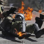 A riot policeman reacts after he was hit by a petrol bomb thrown by protesters. (AP Photo/Petros Giannakouris)