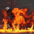 A riot policeman is on fire from a petrol bomb thrown by protesters. (AP Photo/Thanassis Stavrakis)