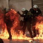 A fire bomb explodes among riot police during a nationwide general strike in Athens. (AP Photo/Nikolas Giakoumidis)