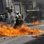 A fire bomb explodes among riot police during clashes. (AP Photo/Nikolas Giakoumidis)
