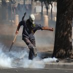 A protester kicks a tear gas canister towards riot police. (AP Photo/Thanassis Stavrakis)