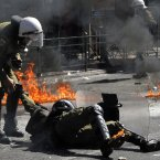 A riot policeman assists a colleague after he was hit by a petrol bomb thrown by protester. (AP Photo/Nikolas Giakoumidis)