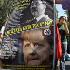 A protester holds a poster with photographs of Nazi leader Adolf Hitler and German Chancellor Angela Merkel during a nationwide general strike. (AP Photo/Thanassis Stavrakis)