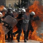 A fire bomb explodes among riot police during clashes in Athens. (AP Photo/Nikolas Giakoumidis)