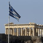 The Greek and European flags are seen with the Parthenon of the Acropolis hill in the background prior to a mass anti-government protest, in central Athens. (AP Photo/Dimitri Messinis)
