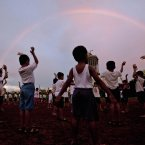 Children perform exercises in a park as a rainbow appears in the background in Mumbai, India. (AP Photo/ Rajanish Kakade)