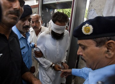 Pakistani police officers escort blindfolded Muslim cleric Khalid Chishti to appear in court in Islamabad, Pakistan, Sunday, Sept. 2