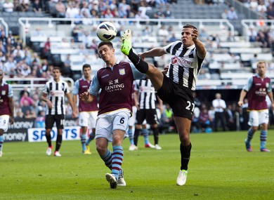 Newcastle United's Steven Taylor tries to control the ball under pressure from Aston Villa's Ciaran Clark.